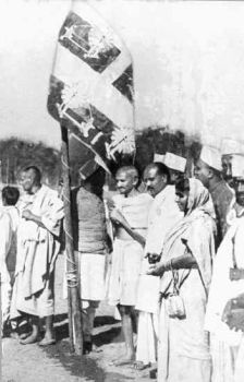 Gandhiji hoisting the Indian flag with the charka at the Lahore session of the Indian National Congress, December 1929.