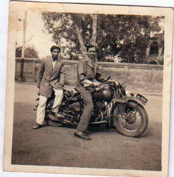Flying Officer J. M. Massey on his Harley Davidson motorcycle with his orderly, Nazir. 1947